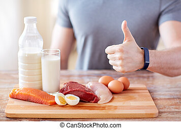 man with food rich in protein showing thumbs up - sport, ...
