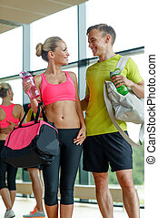 smiling couple with water bottles in gym