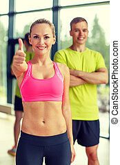 smiling man and woman showing thumbs up in gym