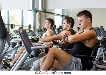men working out on exercise bike in gym