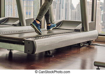 sport, fitness, lifestyle, technology and people concept - woman exercising on treadmill in gym against the background of a big city