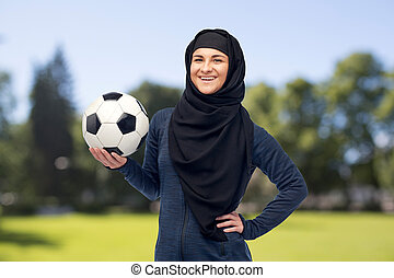 happy muslim woman in hijab with football