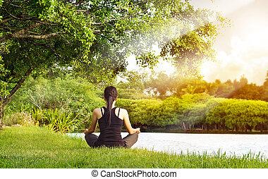 Sport girl meditating in nature green park at the sunrise