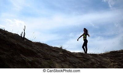 sport girl stands on a Sandy Hill