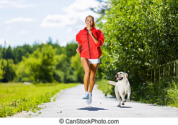 Sport girl - Young attractive sport girl running with dog in...