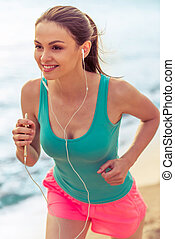 Sport girl with gadget on the beach