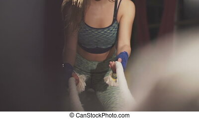 Sport girl working out with ropes in the dark gym. Slowly