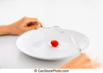 woman with plate and one tomato