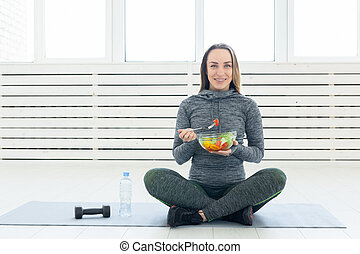 Sport, healthy lifestyle and people concept - young woman with salad and a dumbbell sitting on the floor