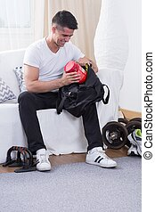 Sport in daily life - Happy athletic man sitting on sofa at...