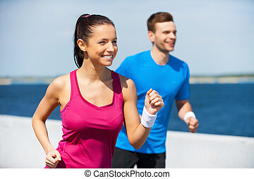 Sport is our life.  Cheerful young woman and man in sports clothing running along the riverbank  and smiling