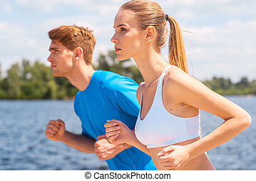 Sport is our life.  Cheerful young woman and man in sports clothing running along the riverbank