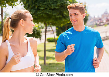 Sport is our life.  Cheerful young woman and man in sports clothing running along the road and smiling