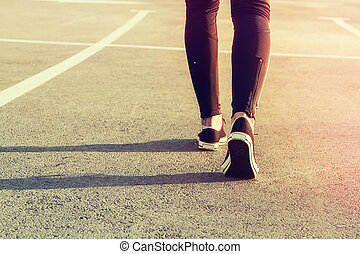 sport legs girl sneakers on the pavement