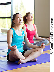 smiling women meditating on mat in gym