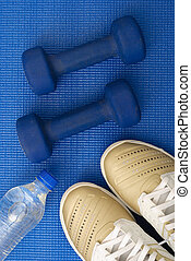 Flat lay shot of Sport equipment on yoga mat. Equipment for jogging, yoga, stretching, pilates