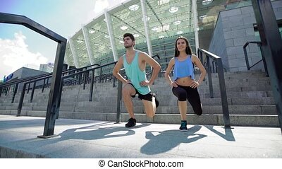 Sport, people, exercising and lifestyle concept - couple doing squats on city street stairs