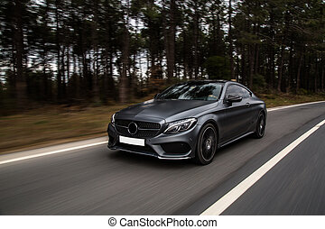 Sport sedan driving on the road. front view, drive accross forest