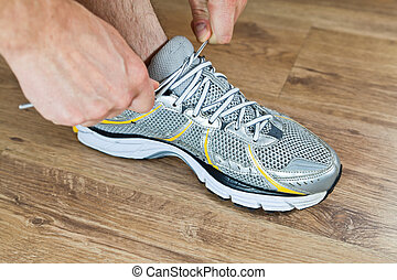 Sport shoe tying, exercise at gym - Man tying sports shoe at...