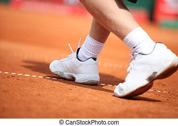 Sport-Shoes - A man runs over the tennis court with with...
