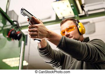 Shooting a gun at shooting range