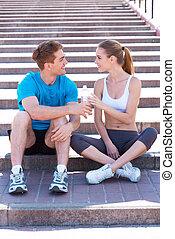 sport, verbinden, leute., seitenansicht, von, schöne , junges, in, sportarten-kleidung, sitzen treppe, voreinander, und, lächeln
