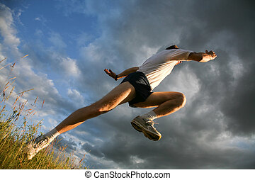 Sport - View from below: athlete raising leg and hand