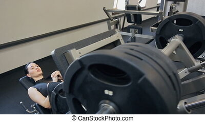 Sport woman doing exercises sitting on trainer in gym