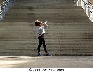 Sport woman drinking water from bottle - Full length ...