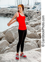 Sport woman on the rocky beach