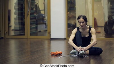 Sport woman sitting on floor, tie shoelaces inside fitness studio