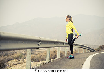 sport woman stretching leg muscle after running workout on asphalt road with dry desert landscape in hard fitness training session