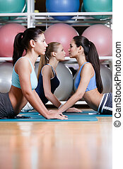 Sport women doing stretching exercise on mats