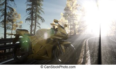 sportbike on tre road in forest with sun beams