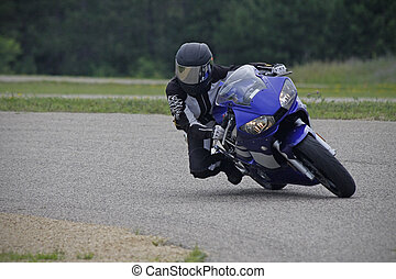 A female sportbike rider aggressively enters a turn at the race track