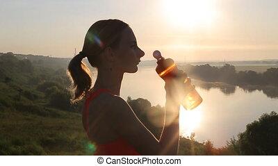 sportif, femme, eau potable, à, coucher soleil, après, running., lent, motion.