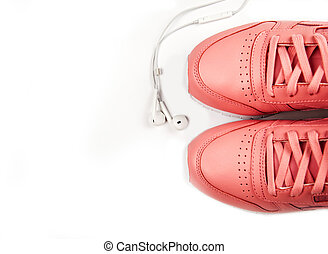 Sporting pink sneakers on a white background with headphones. Training. Sport