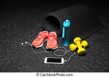 Sportive accessories for gym training. Sport shoes, dumbbells, bottle, and smart phone on a black background. Copy space.