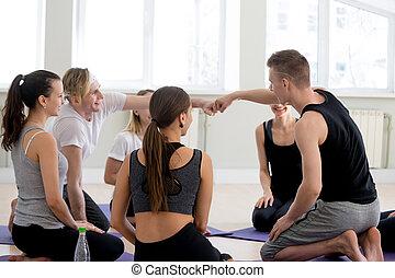 Sportive athletic people at meeting in gym studio