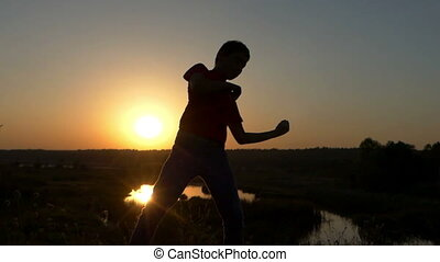 Sportive Boy Trains Boxing Blows on a Lake Bank at Sunset in Autumn in Slo-Mo