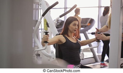 Sportive brunette does exercises in gym with personal trainer.