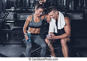 sportive couple with smartphone - sportive couple using...