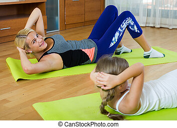 Sportive family of two having aerobics class at home - Young...