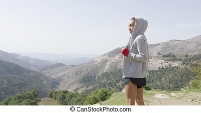 Sportive female boxer on top of mountain