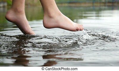 Sportive female legs are swinging touching water in a lake...
