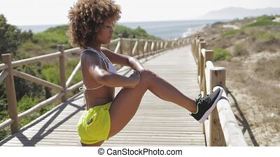 Sportive girl training on tropical pier - Side view of ...