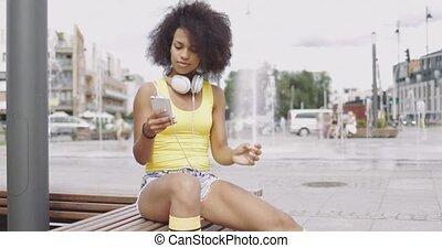 Sportive girl using smartphone on bench - Beautiful ethnic...