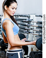 Sportive girl with dumbbells in sport centre