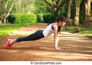 Sportive girl working out doing push ups press exercise in...
