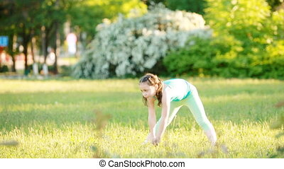 Sportive little girl doing a cartwheel on the meadow in the summer park.